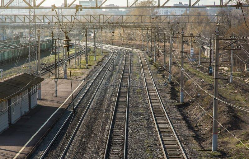 railways двухгусеничные рельсы покидая расстояние и станция стоковое изображение
