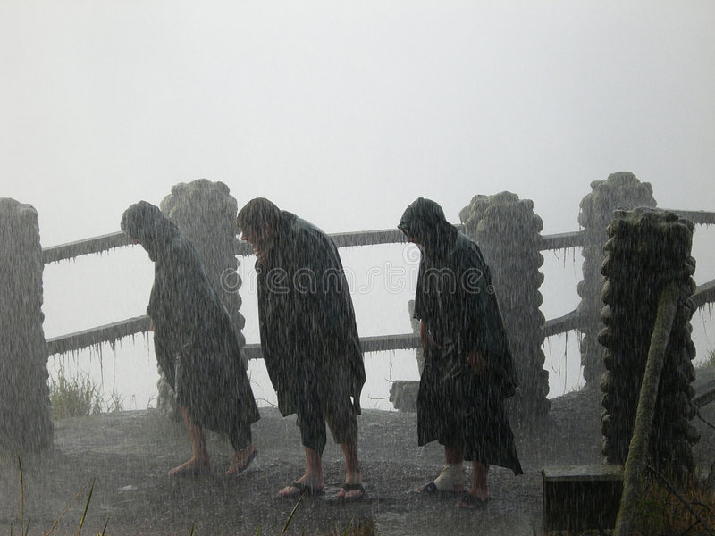 Rain. Image of three people in a rain storm at Victoria Falls in Africa royalty free stock image