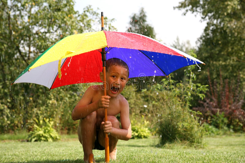 Rain. Little boy under umbrella in summer rain stock photography