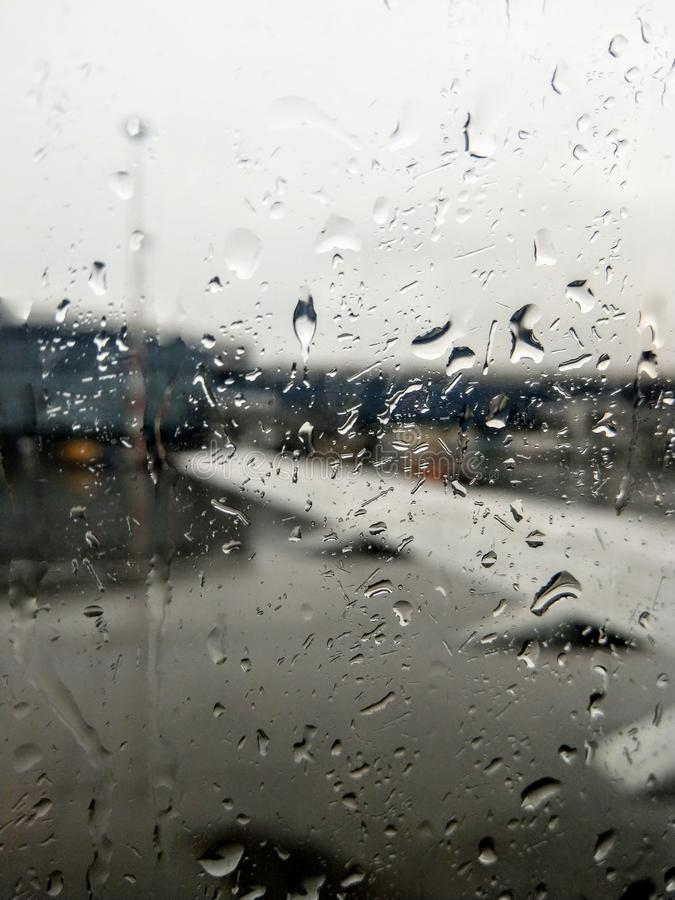 Rain on airplane window. An airplane window with a blurred view of an airport with rain drops on the window panel. weather season traveling travelling clouds stock images