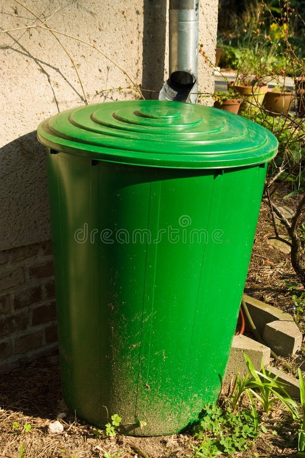 Rain barrel. In a garden stock image