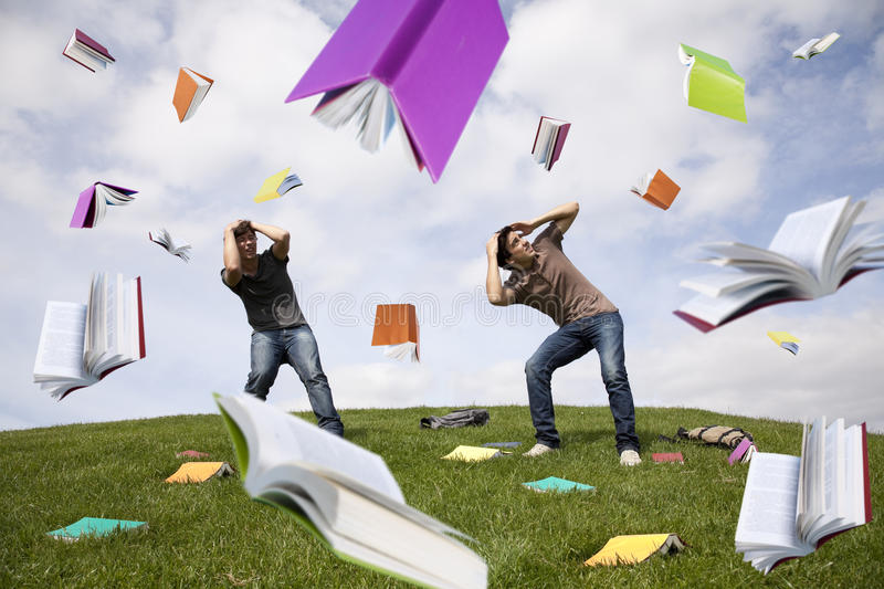 Rain of books. Teenager students outside protecting there heads from a rain of books stock image
