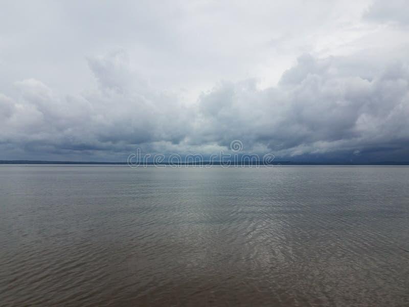 Rain clouds forming over calm river near shore stock photo