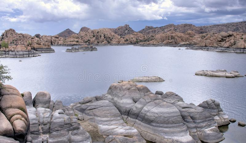 Lake Watson Granite Dells, Prescott Arizona USA. Rain clouds over granite cliffs and boulders of Watson Lake and distant mountains. Lake Watson is one of two royalty free stock photography