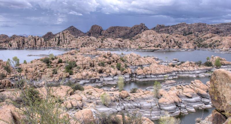 Lake Watson Granite Dells, Prescott Arizona USA. Rain clouds over granite cliffs and boulders of Watson Lake and distant mountains. Lake Watson is one of two royalty free stock photo