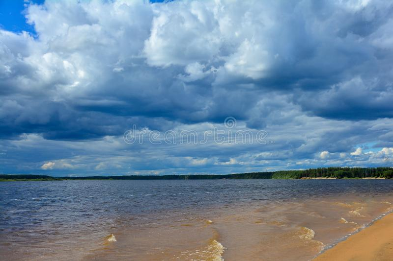 Rain clouds over the river. The wet sand of the beach. Surf of the waves. Forest shore on the horizon royalty free stock images