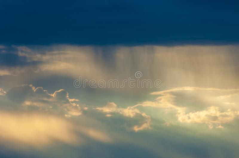The rain comes from the clouds. The rays of the sun make their w. Ay through the clouds. Dramatic photography stock image