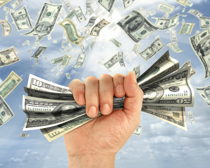 Rain of dollars. Wealth idea in a metaphor of rain of dollars. The hand holds some dollars stock photography