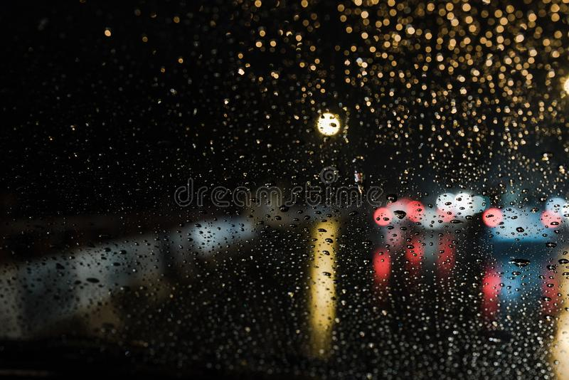 Rain Drop on car windshield. Abstract backgroud with real life rain drops from car windshield on heavy traffic lights royalty free stock image