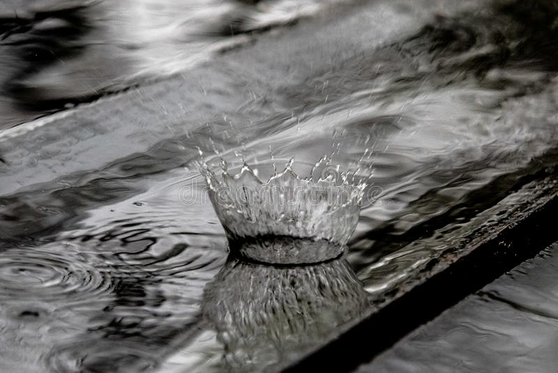 Rain drop splash in wooden floor bouncing and shaping a water crown stock images
