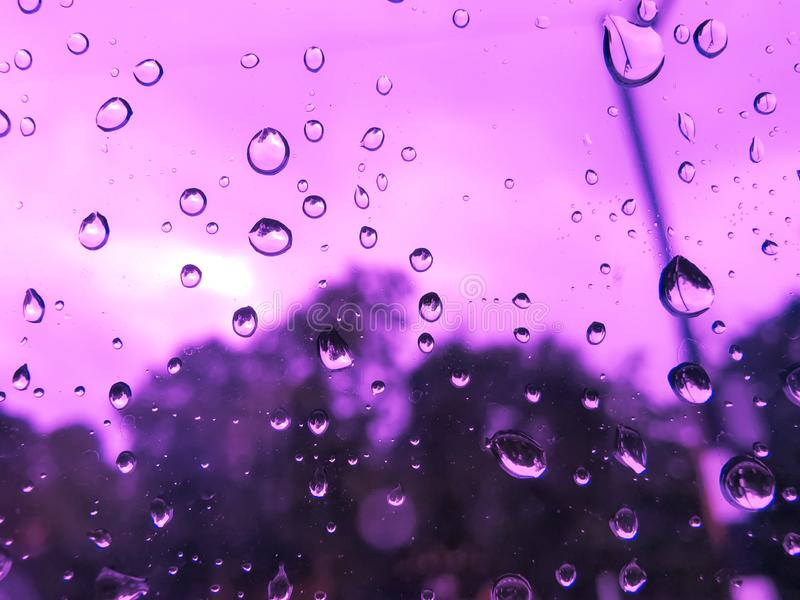 Rain drop on window car in purple light. Water Splash on glass. Rainy season, close up stock images