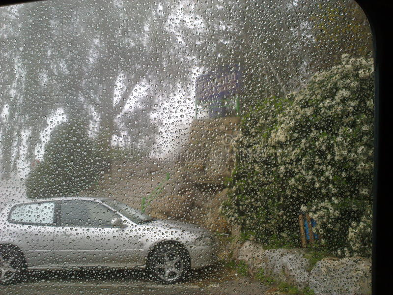 Rain droplets on car windshield stock images
