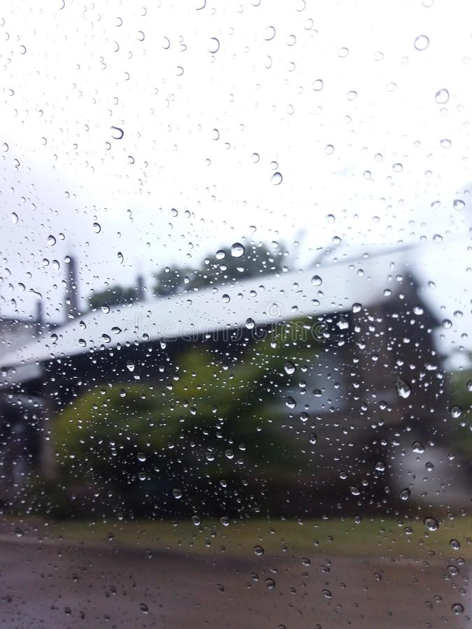 Rain droplets on a clear glass window. With a blurry house as background royalty free stock photo