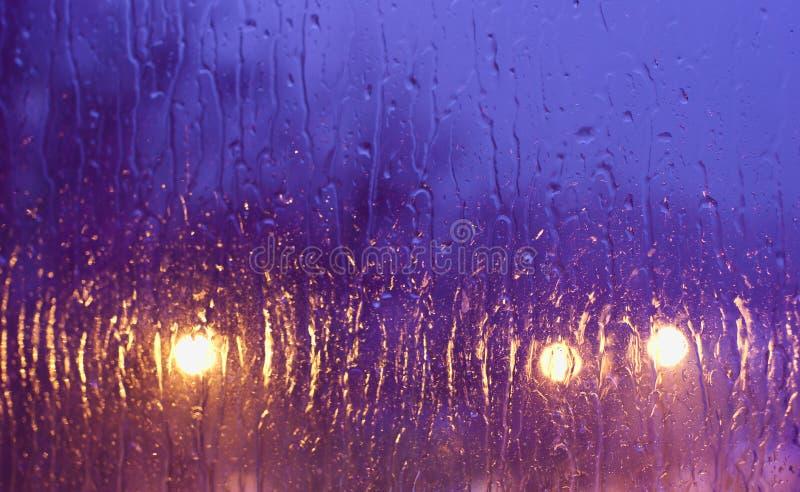 Rain droppar på fönstret på nattlampabakgrund arkivbilder