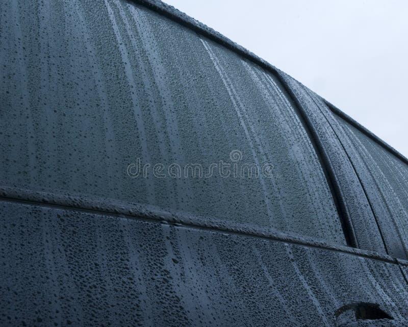Rain drops on a black car stock images