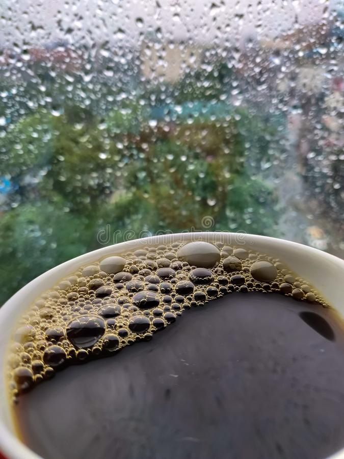 Rain drops and black coffee. Black coffee and the rain drops on the glass of the window