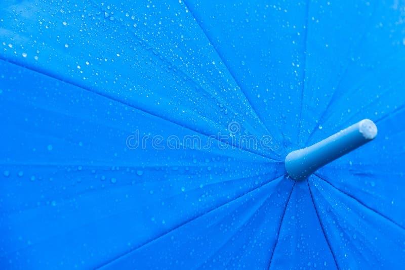 Rain drops on a blue umbrella. Rain drops on a blue umbrella stock photo