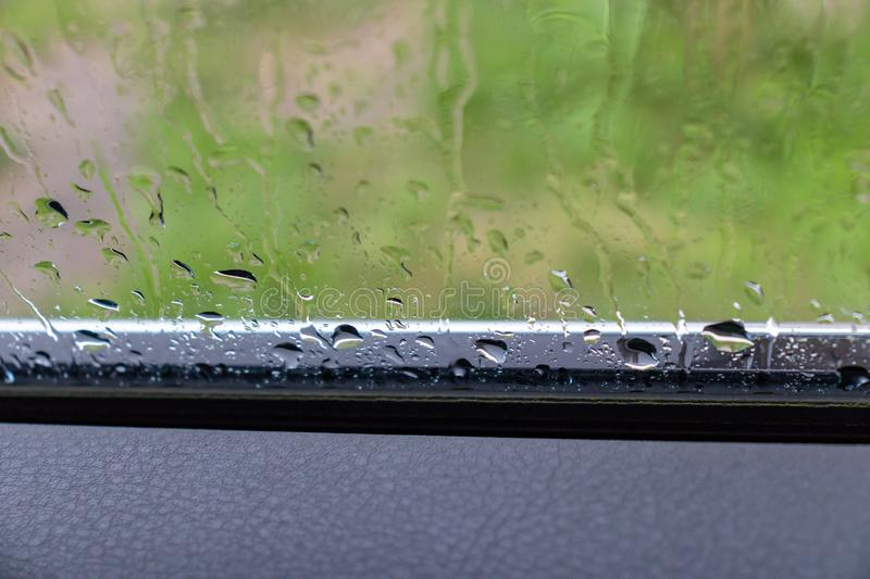 Rain drops on car glass in rainy day, summer is over and autumn fall storms and bad weather comes.  stock photo