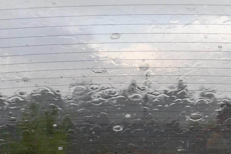 Rain drops on car glass in rainy day, summer is over and autumn fall storms and bad weather comes.  stock images