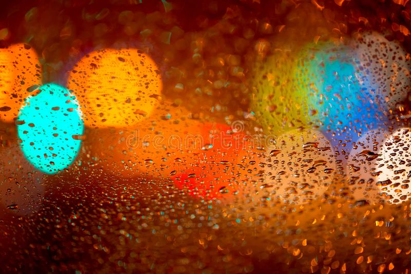 Rain drops on car window with road light bokeh Abstract night city life background at night during rainy season royalty free stock images
