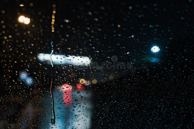 Rain Drops from car windshield. Real life rain drops from car windshield with traffic lights background stock image