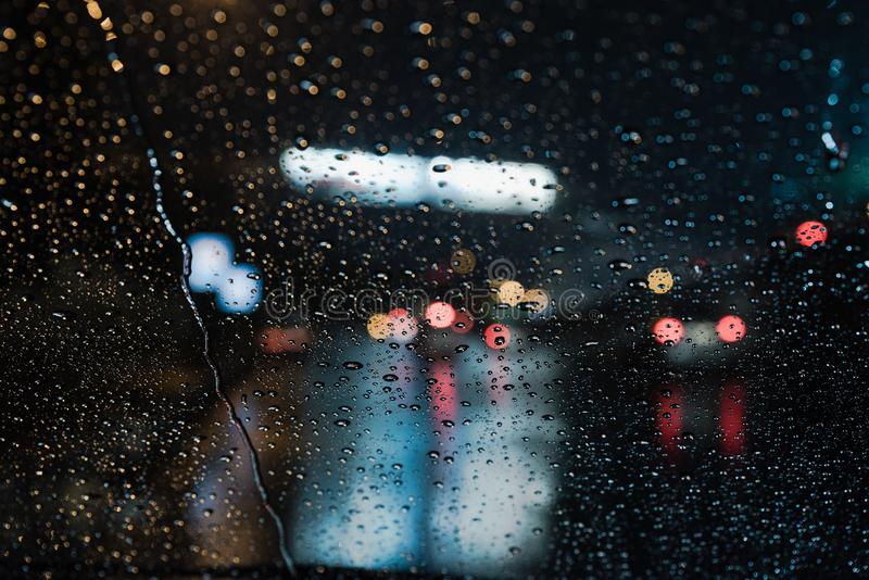 Rain Drops from car windshield. Real life rain drops from car windshield with traffic lights background royalty free stock images