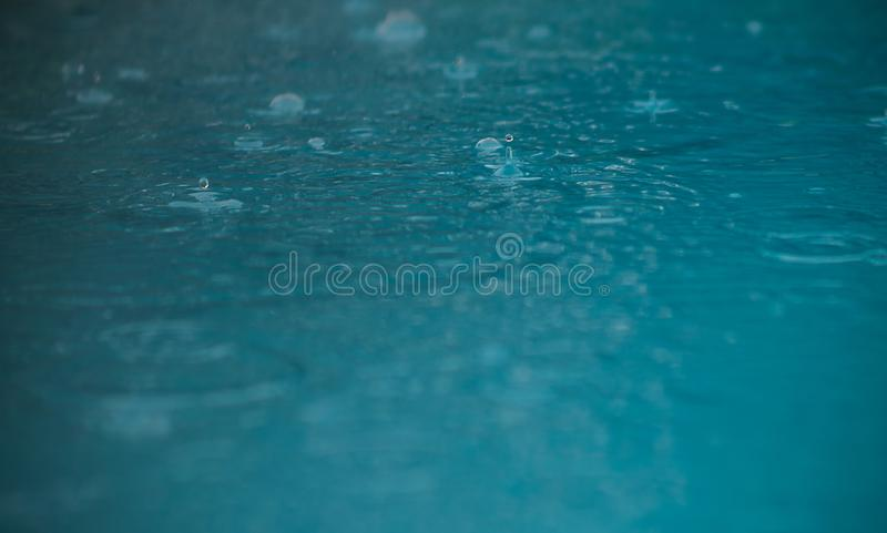 Rain drops falling in to the water royalty free stock photography