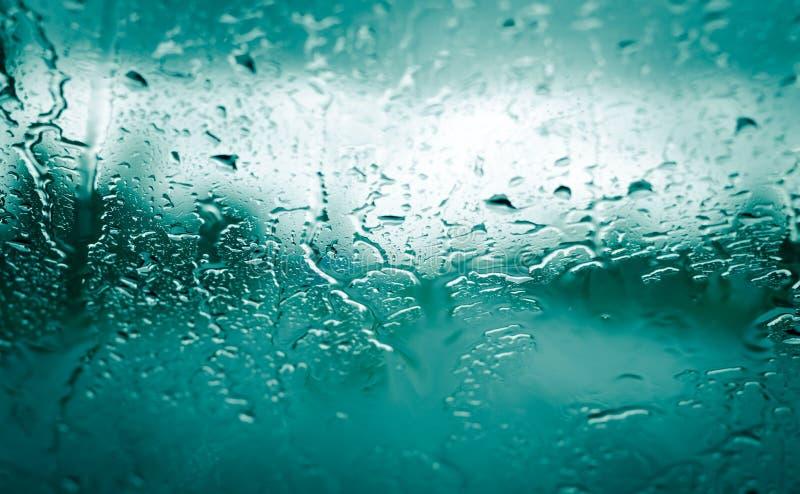 Rain drops on front car green glass stock photos