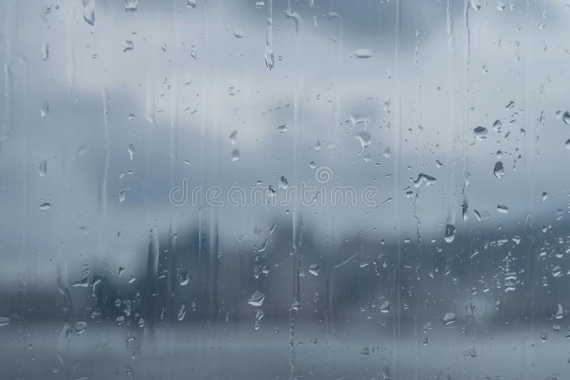 Windowpane with rain drops through which the panorama of the big city and the sky with clouds is visible, the modern city royalty free stock photo