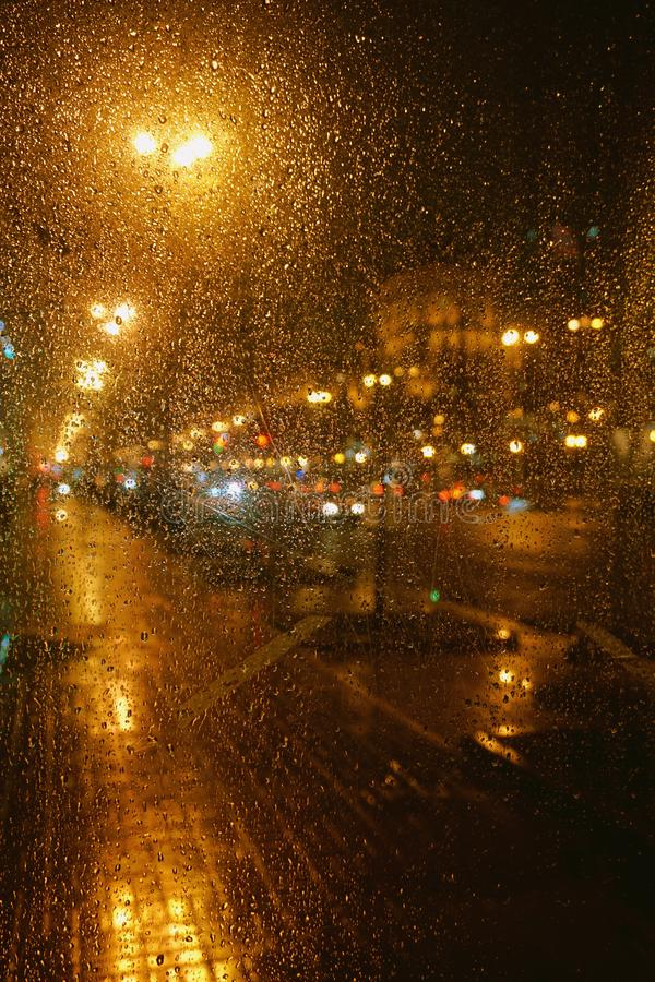 Rain drops on glass surface with bokeh night city lights from lanterns. Car, shops stock photography