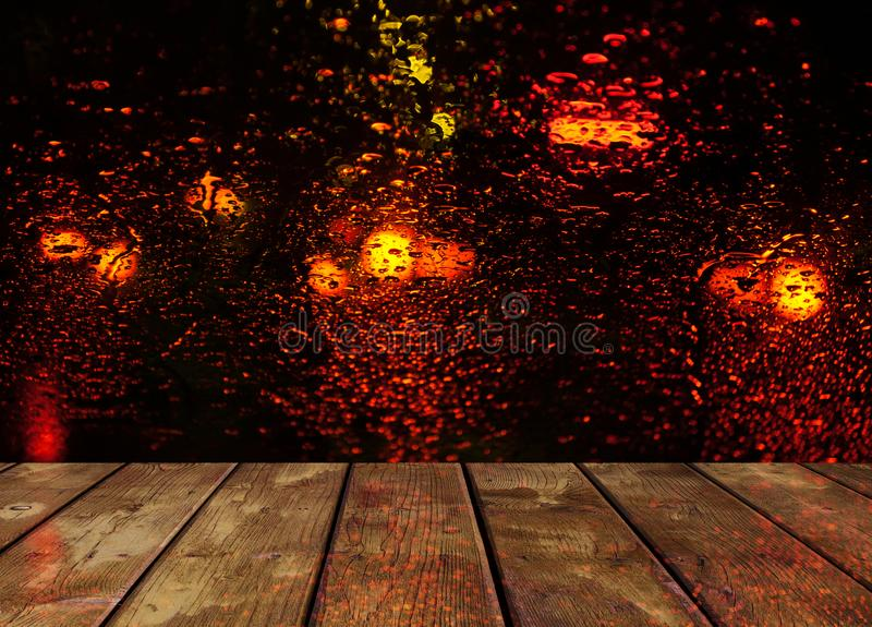 Rain drops on glass surface with red bokeh night city lights with wooden table.  royalty free stock photos