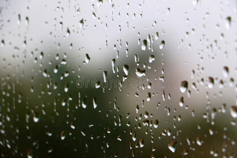 Rain drops on glass window. During day time thunder shower rain storm royalty free stock image
