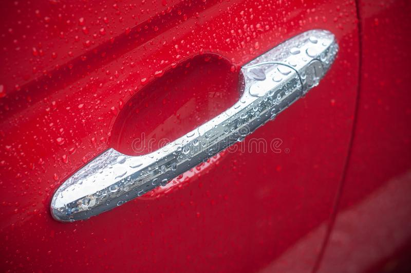 Rain drops on metallic handle on red car stock image