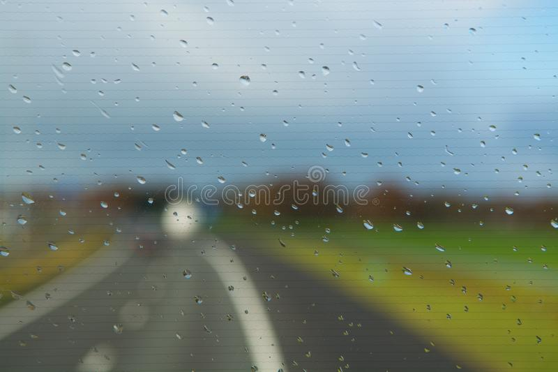 Rain drops op windshield, driving on highway. During bad weather royalty free stock photography