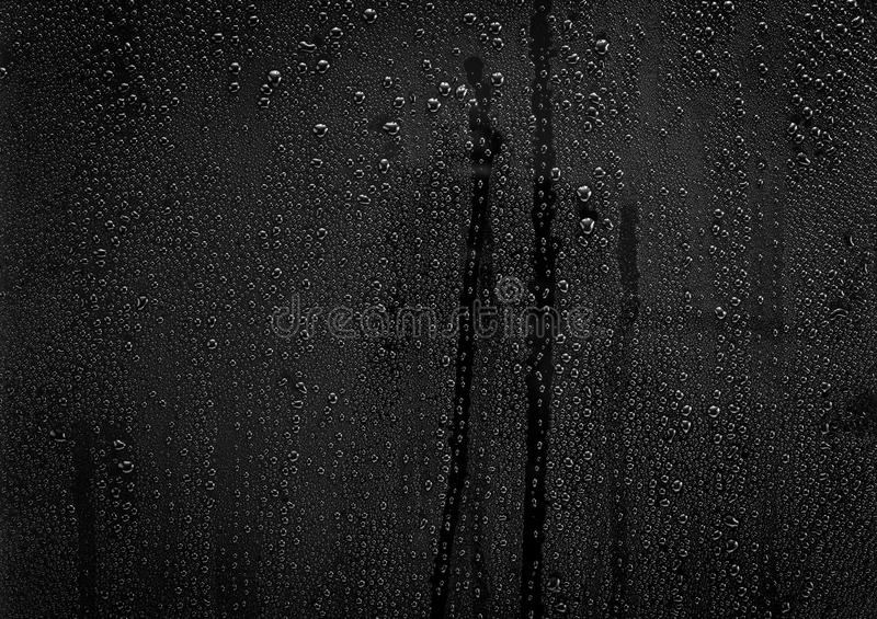 Rain drops pattern on glass. Rain drops pattern on black glass surface for background and texture material royalty free stock image