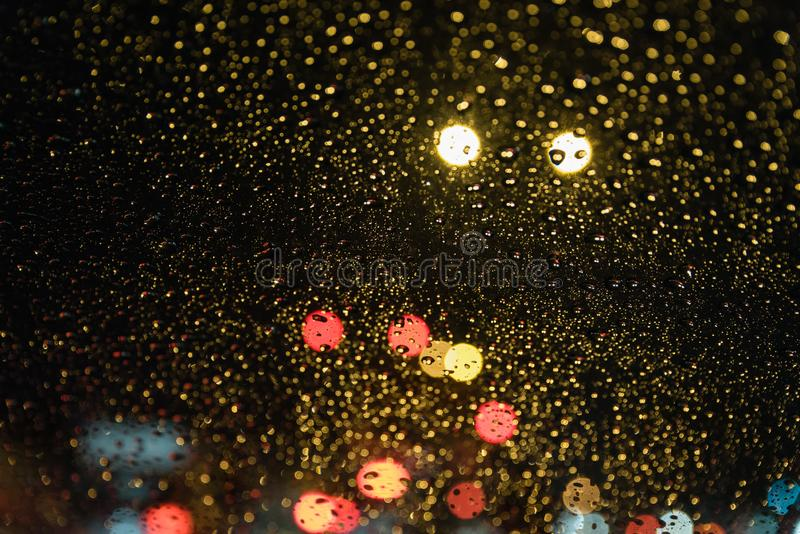 Rain Drops from real life scene. Real life rain drops scene taken from inside car windshield traffic lights background royalty free stock photography
