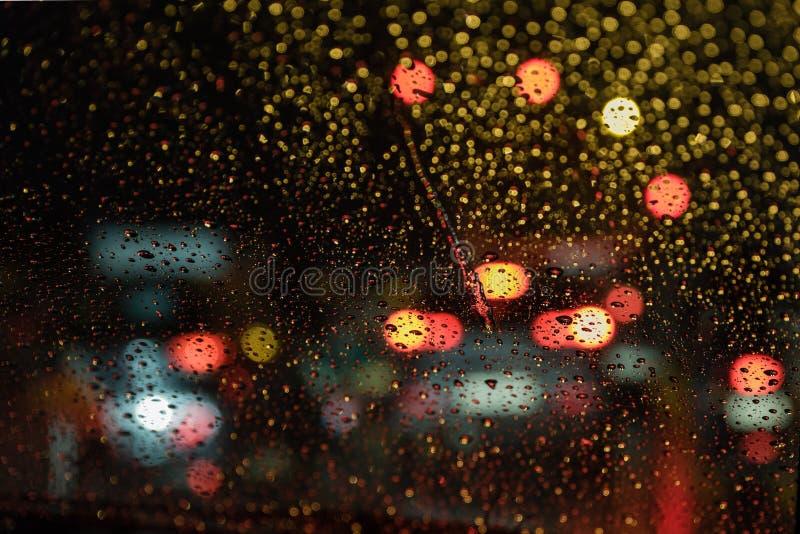 Rain Drops from real life scene. Real life rain drops scene taken from inside car windshield traffic lights background stock image