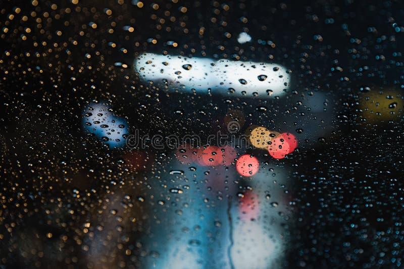 Rain Drops from real life scene. Real life rain drops scene taken from inside car windshield traffic lights background stock photo