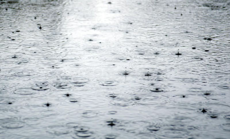 Rain drops rippling in a puddle . stock photo