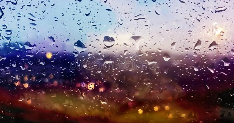 Rain drops on the surface of clear glass with sunset bokeh background. royalty free stock photography
