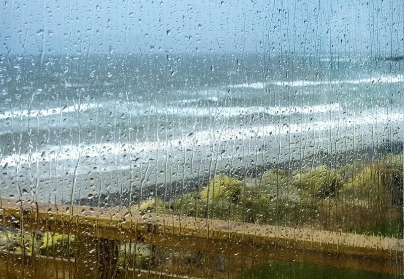 Rain drops on a window. Autumn rain drops on a window, rough seas in the background royalty free stock image