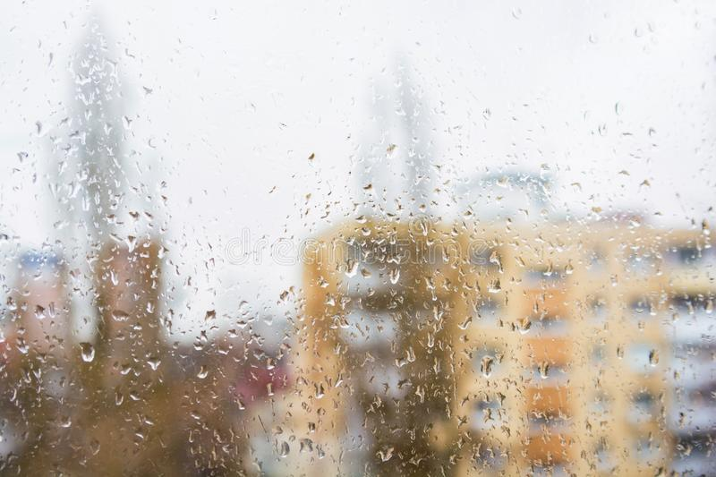 Rain drops on window glass surface with modern appartment building in background. Rain drops on window glasses surface with with modern appartment building in stock photo