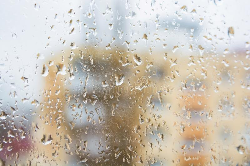 Rain drops on window glass surface with modern appartment building in background. Rain drops on window glasses surface with with modern appartment building in stock photography