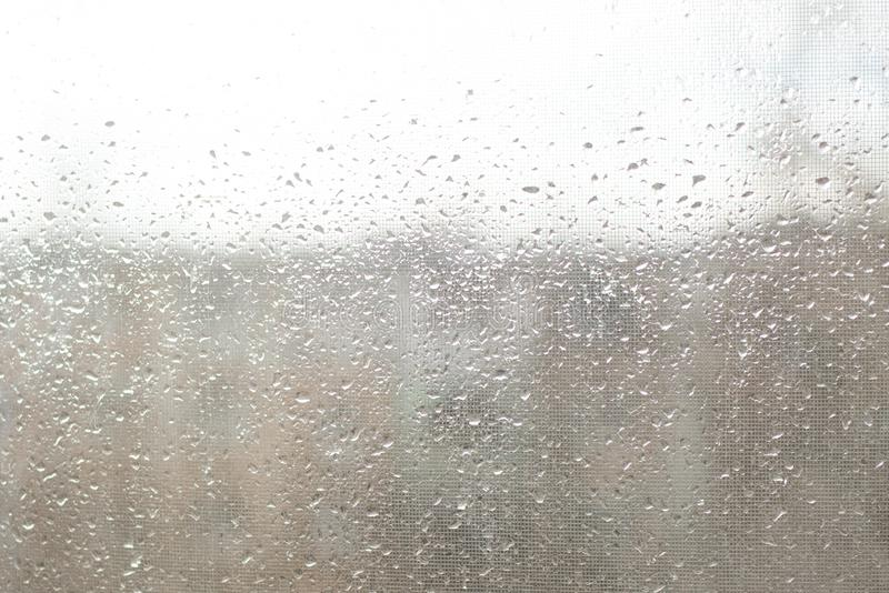 Rain drops on window glasses surface with cloudy background . Natural Pattern of raindrops. Isolated on cloudy background royalty free stock images