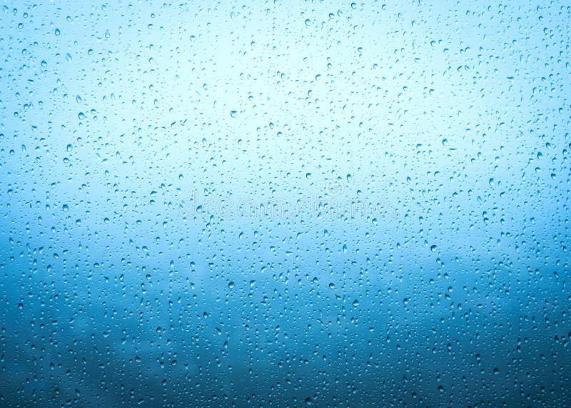 Rain drops on window glasses surface with sky cloudy background royalty free stock photography