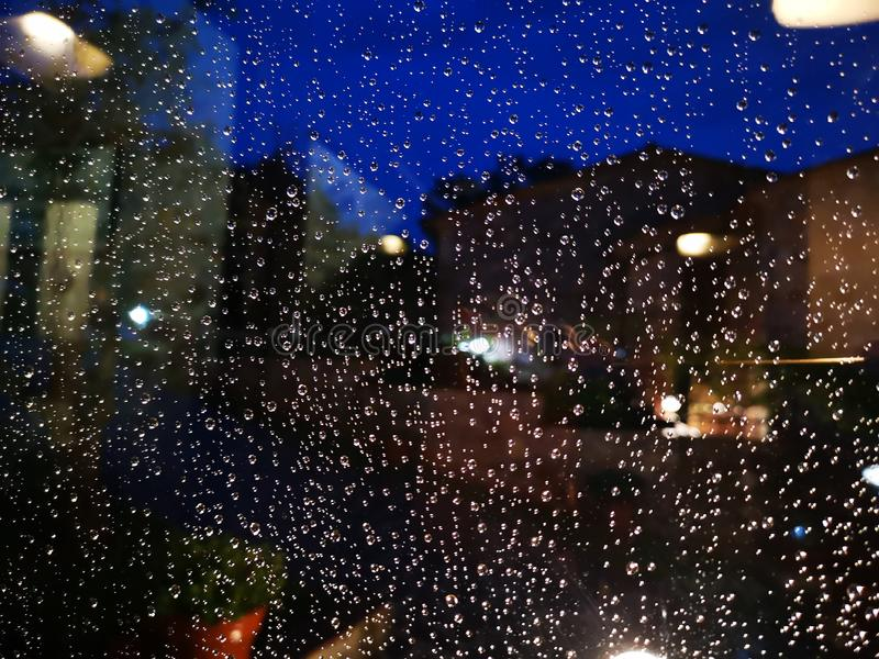Rain drops on the window. Rain drops window lights night wet background illuminated water liquid rain-drop water-drop droplet detail royalty free stock photos