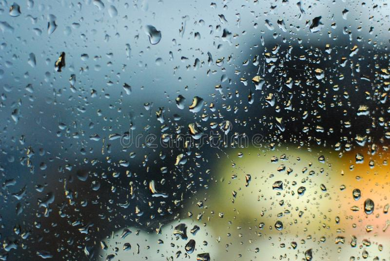 Rain drops on window with road light bokeh background.  stock photos