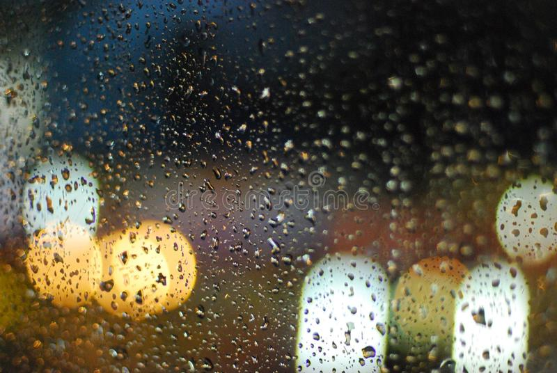 Rain drops on window with road light bokeh background stock images