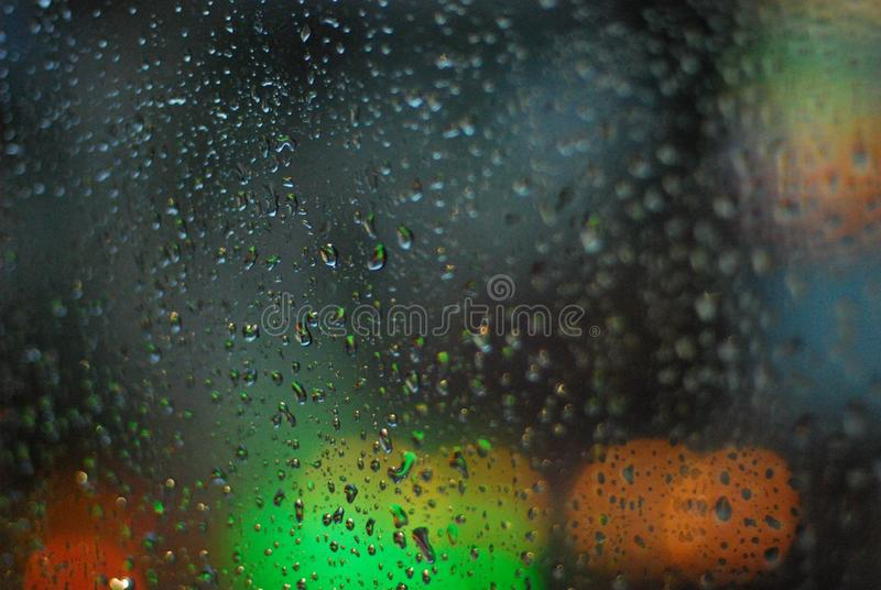 Rain drops on window with road light bokeh background royalty free stock photo