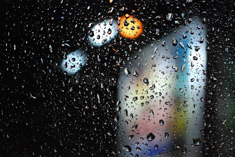 Rain drops on window with road light bokeh background royalty free stock image